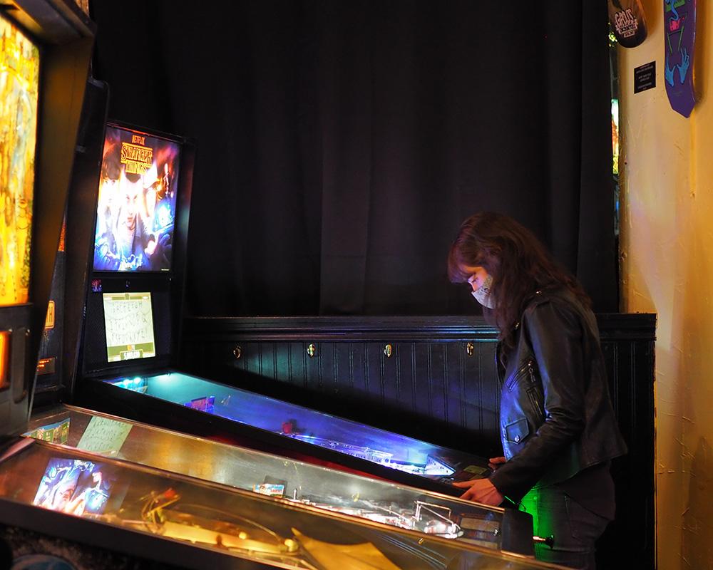 Woman playing Stranger Things pinball machine at Wedgehead